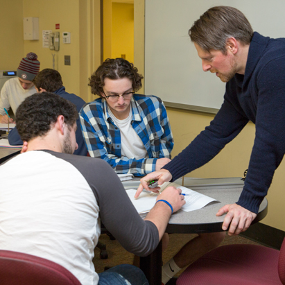 two students working with a professor