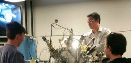 a professor and two students working with a complex apparatus.