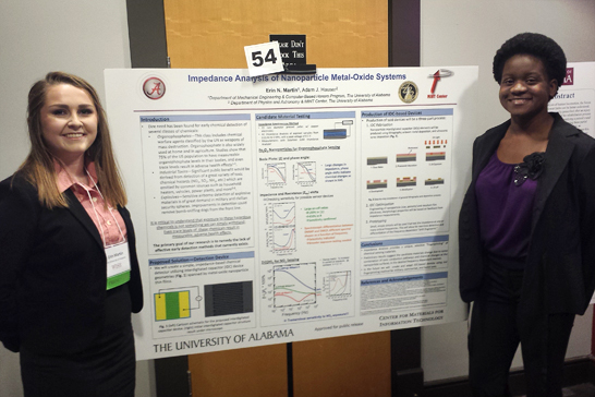 two female students stand next to their research poster presentation