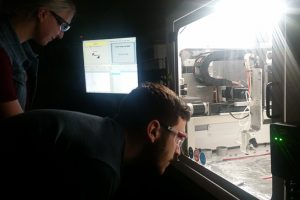 two researchers looking through a window at an array of equipment