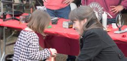 faculty member Dr. Claudia Mewes doing a physics demonstration for a little girl.