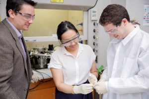 Dr. Adam Hauser working with two students in his lab