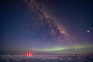 The IceCube Observatory near the South Pole with the southern lights visible in the sky