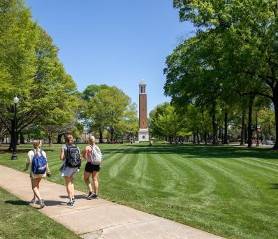 three students walking on the Quad past Denny Chimes